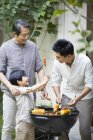 Chinese male multi-generation family barbecuing in courtyard — Stock Photo
