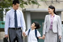 Chinese schoolboy walking with parents on street — Stock Photo