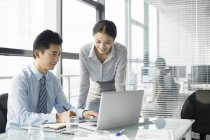 Chinese business people using laptop in office — Stock Photo