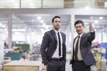 Uomini d'affari in piedi in fabbrica e guardando a macchina fotografica — Foto stock