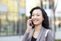 Chinese woman talking on phone on street — Stock Photo