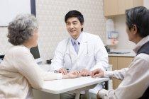 Médecin chinois prenant pouls de la femme âgée — Photo de stock