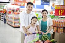 Chinese family posing with shopping cart in supermarket — Stock Photo