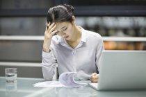 Уставшая китайская предпринимательница работает с документами в офисе — стоковое фото