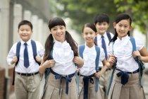 Écoliers chinois en uniforme scolaire, posant sur la rue — Photo de stock