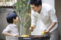Китайский отец и сын барбекю во дворе — стоковое фото