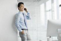 Hombre de negocios chino apoyado en la pared y hablando por teléfono en la oficina - foto de stock
