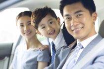 Китайская пара с сыном, езда в автомобиле вместе — стоковое фото