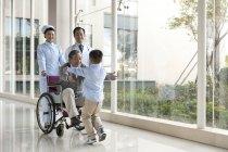 Petit-fils de chinois en cours d'exécution au grand-père en fauteuil roulant avec des médecins — Photo de stock