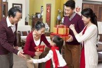 Família com garota visitando os avós com presentes durante o ano novo chinês — Fotografia de Stock