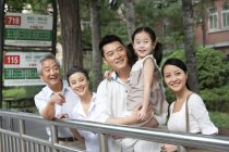 Chinese family with daughter waiting at bus stop — Stock Photo