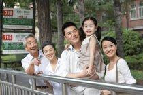 Chinesische Familie mit Tochter warten an der Bushaltestelle — Stockfoto