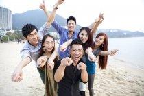 Amici cinesi che punta e guardando a porte chiuse sulla spiaggia di Repulse Bay, Hong Kong — Foto stock