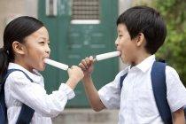 Enfants chinois manger pops glacés sur la rue — Photo de stock