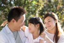 Happy Chinese parents carrying daughter in park — Stock Photo