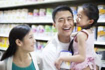Chinese man holding daughter in supermarket — Stock Photo