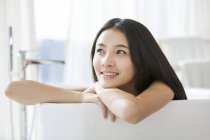 Chinese woman lying in bathtub and looking away — Stock Photo