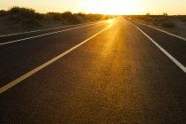 Estrada passando por área selvagem no pôr do sol brilhante, China — Fotografia de Stock