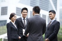 Chinese working team discussing business on street — Stock Photo