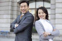 Уверенные китайские бизнесмены, стоящие спиной к спине в финансовом районе — стоковое фото