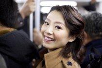 Femme chinoise joyeuse dans la rame de métro — Photo de stock