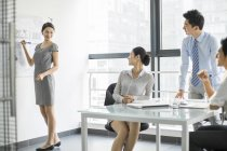 Chinese business people talking at meeting in board room — Stock Photo