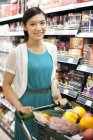 Chinese woman with shopping cart in supermarket — Stock Photo