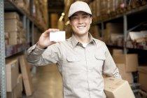 Hombre chino almacén trabajador celebración en blanco tarjeta de visita - foto de stock