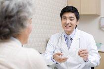 Chinesischer Arzt erklärt Patientin Medikamentendosis — Stockfoto