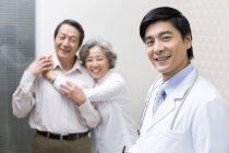 Médico chino con abrazos pareja senior en el hospital - foto de stock
