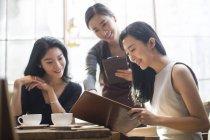 Amis chinois commande avec serveuse au café — Photo de stock