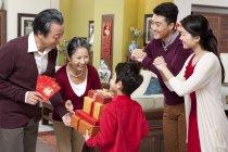Kleiner Junge mit Eltern, Großeltern mit Geschenken während Chinese New Year zu besuchen — Stockfoto