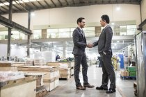 Businessmen shaking hands at industrial factory — Stock Photo