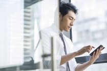 Chinese businessman using smartphone in doorway at office — Stock Photo