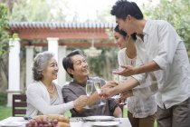 Happy Chinese family celebrating with champagne outdoors — Stock Photo