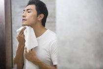 Китаец растирает лицо полотенцем — стоковое фото