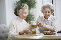Senior Chinese women smiling and pouring tea — Stock Photo