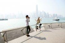 Китаец фотографирует молодую женщину с камерой в гавани Виктория, Гонконг — стоковое фото