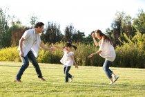 Familia China con hija jugando en la pradera de verano - foto de stock