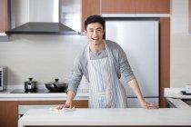 Chinês jovem cozinha limpeza com pano e olhando na câmera — Fotografia de Stock