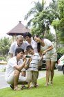 Chinese man filming with multi-generation family on vacation — Stock Photo
