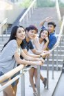 Chinese friends leaning on balustrade and posing on street — Stock Photo