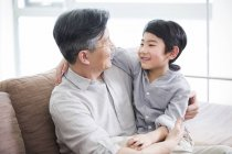 Chinese grandson sitting on grandfather lap and smiling in home interior — Stock Photo