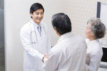 Chinesische älteres paar Händeschütteln mit Arzt im Krankenhaus — Stockfoto