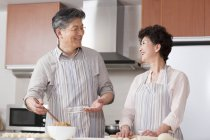 Senior Chinese couple making dumplings together in kitchen — Stock Photo
