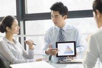 Empresários chineses usando tablet digital no escritório — Fotografia de Stock