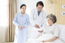 Travailleurs médicaux chinois parlant avec le patient à l'hôpital — Photo de stock