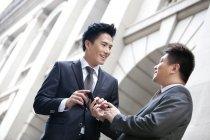 Collègues de travail chinois avec le smartphone en face de l'immeuble — Photo de stock