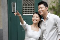Chinese couple embracing on street and pointing at view — Stock Photo