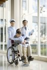 Chinese grandson embracing grandfather in wheelchair with doctors — Stock Photo